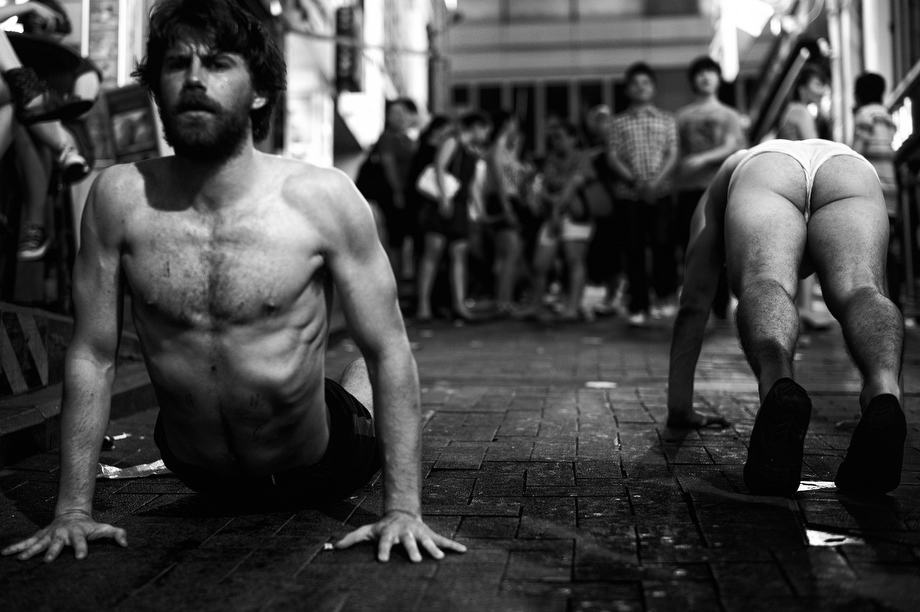 Two half naked guys doing strange exercises at Lan Kwai Fong