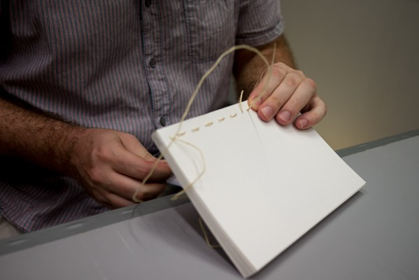 Jay Komuda binding his dummy using traditional hand-stitching.