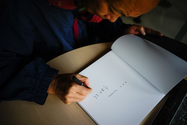 Yunnan Photographer Geng Yunsheng signing his photo book.