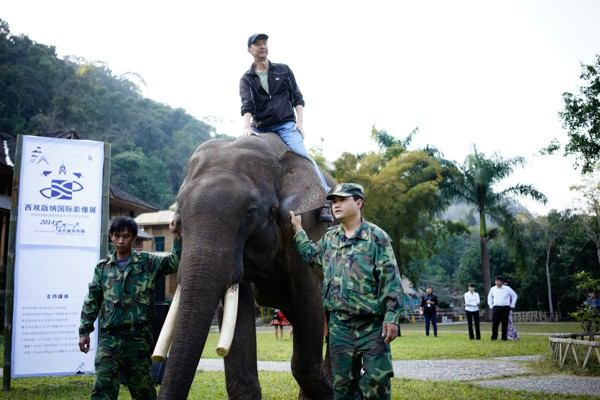 Parisian Chinese photographer Zeng Nian rides an elephant to collect his award.