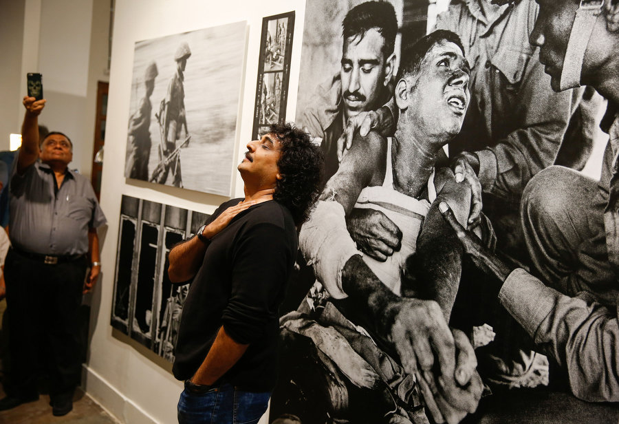 "Swapan Parekh, son of the late Kishore Parekh, at his father's exhibition ""Bangladesh – A Brutal Birth"" at the Delhi Photo Festival 2015. Photograph by Mustafa Quraishi."