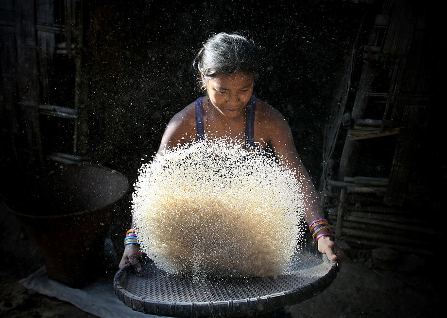 A young Mro women preparing grain in a remote Mro village in Bandarban. Tribal people of hill tracts cultivate Jhum in the stiff hills only one season. After harvesting, they collect and stock the grain for the whole year for their family.