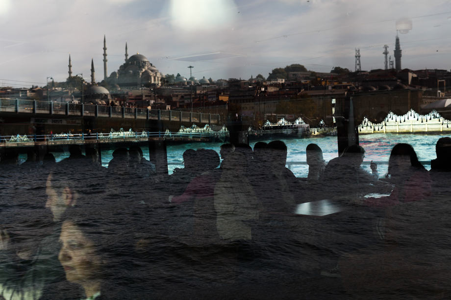 Passengers on a ferry and the historical Sulemaniye Mosque reflected in the glass in Istanbul.
