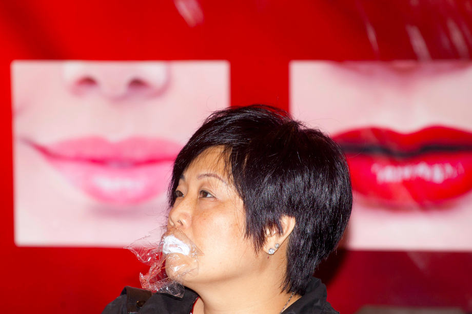The Cosmetics Show 02: A woman waits for her lips treaement process at the Cosmetics Show in Hong Kong.