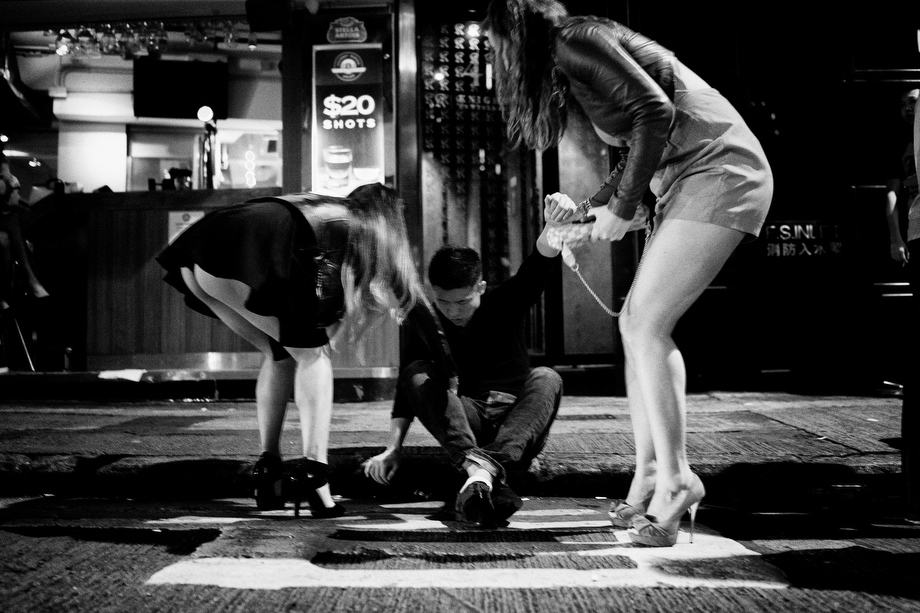 Two atractive girls are helping drunked guy to stand up