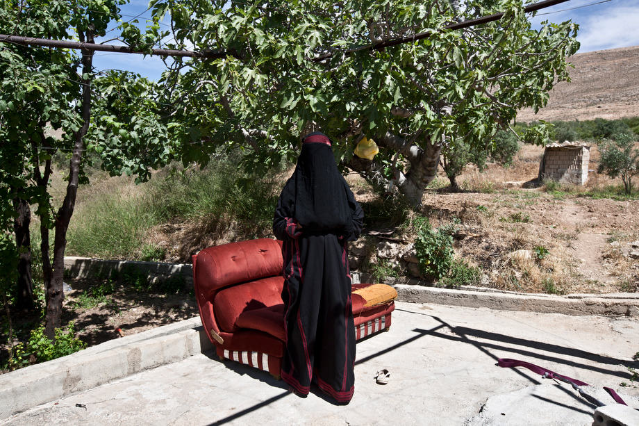 "Lebanon - Jdeideh - Najiba, 63 years old, comes from the village of Soran, North of Hama. She arrived in Lebanon eleven months ago, after the first protests erupted in Hama. ""The Army was shooting at everyone, I remember seeing 50 or 60 people dead"". She now lives in a concrete shed, in an orchard on the outskirts of Jdeideh. In exchange of looking after the trees, she can stay for free. ""I would go back to Syria tomorrow, if it wasn't for the kids. I am very worried about their safety"", she explains, pointing at the four grandchildren she lives with."