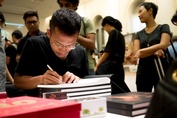 Kim Hak (Cambodia) signing his book during his book launch at the show.