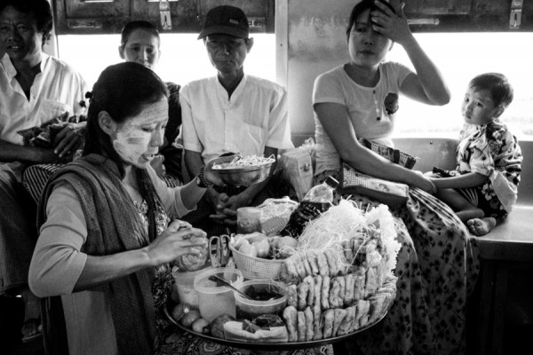 Burmese woman peddling snacks and salads to commuters.