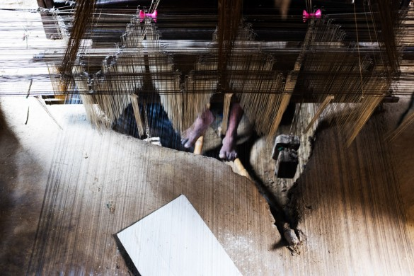 """The loom system is partially embedded into the ground and a pit is made for the weaver to keep his legs. The long hours and varying temperature in the pit results in serious damage to the lower part of the body, leading a weaver to remark:  """"Handlooms today are the graves of living people."""""""