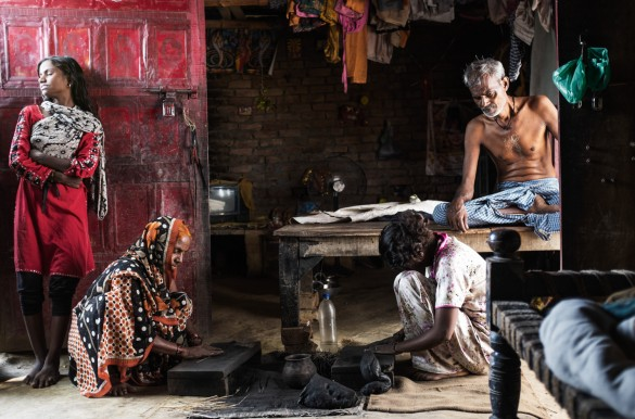 Lali Rajbhar, 65, an unemployed weaver, with his family. His wife and daughters earn a meager living by making incense sticks.