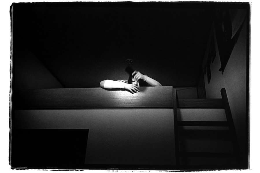 Kaori, 23 years old, relaxes in her room. She rolls bandage to stop bleeding after she cut her arm. IBASYO, © Kosuke Okahara