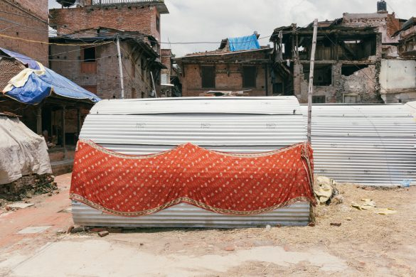 Post-earthquake Tapestry. Red sari sunning against the corrugated iron wall of a makeshift home in Bhaktapur. © Kevin WY Lee.