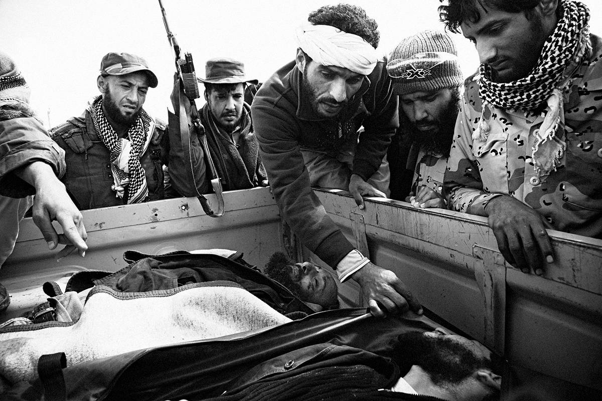 Rebel fighters attempt to identify their dead comrades near the frontline between Ajdabiya and Marsa Brega on April 1, 2011. Photograph © Nicole Tung.