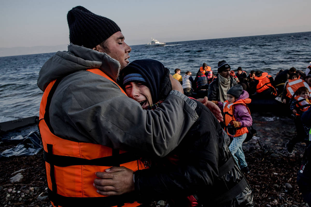 A father comforts his crying son shortly after arriving on the shores of Lesbos, Greece, on November 17, 2015. The roughly 1.5 hour boat ride between Turkey's western coastline and the closest Greek island has cost anywhere between $900-3000 per person. With winter approaching, the weather also becomes more unpredictable, causing further confusion and fear for refugees fleeing conflict.  Over 1 million refugees and migrants have reached Europe's shores this year, overwhelming the continent and presenting the worst refugee crisis since World War II. Many thousands have been fleeing from conflict in Syria, Iraq, and Afghanistan, while thousands of others, from Bangladesh, Iran, and Pakistan seek better livelihoods. The recent  Euro 3bn deal struck between Turkey and the EU, intended to stanch the flow of people, has resulted in Turkish authorities cracking down on the smugglers and rounding up refugees, preventing them from making the sea crossing, but some continue to persist. Photograph © Nicole Tung.